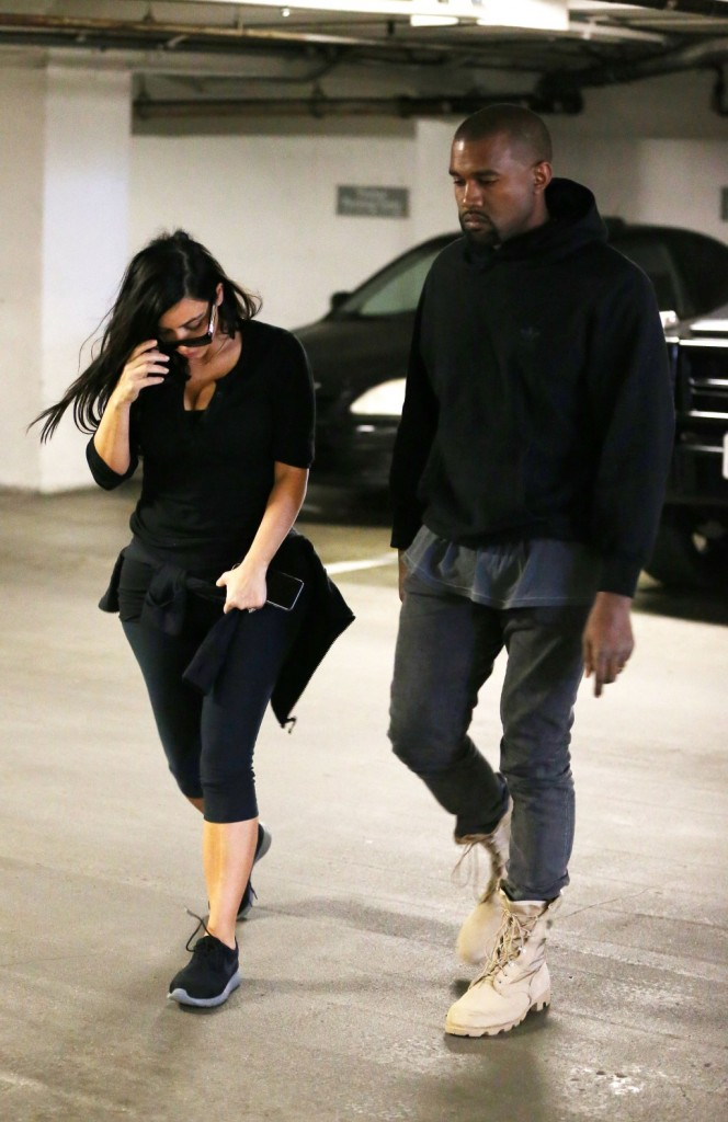 Kim Kardashian and Kanye West walking into a medical building together not looking very happy